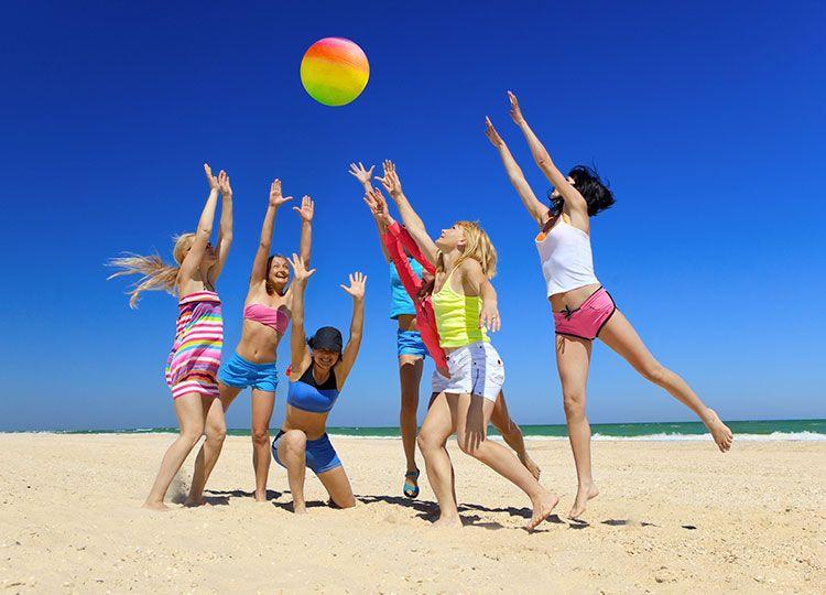 ragazze giocano a beach volley in spiaggia