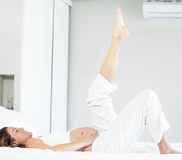 donna in dolce attesa svolge esercizi per le gambe gonfie